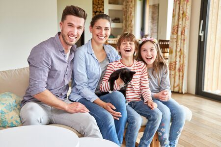Parents and two children with a little cat are sitting happily laughing in the living room