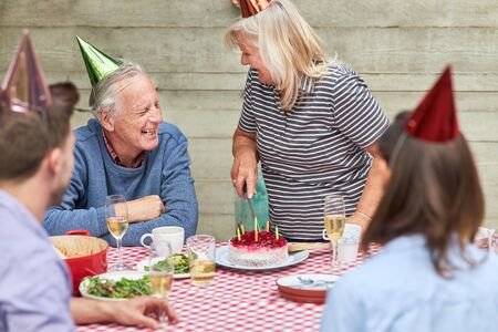 Seniors celebrate with their family birthday with cake in the garden in summer 写真素材