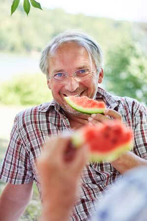 Senior man on a summer outing in nature eating melon