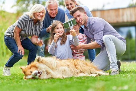 Happy family with grandparents and children makes a selfie in the garden with dog
