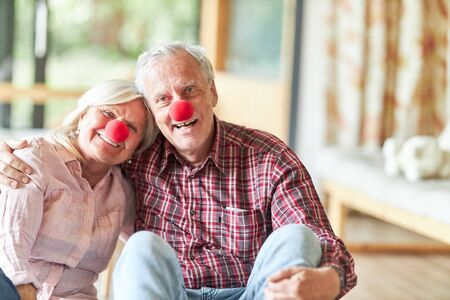 Smiling senior couple with red clown nose in carnival or carnival