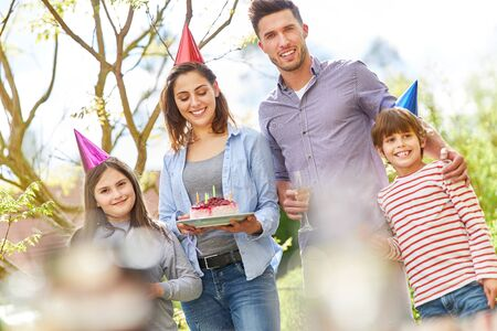 Family with two children celebrate birthday with cake in the garden in summer