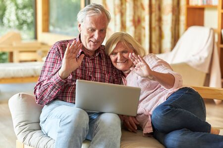 Smiling senior couple watching video chat on laptop computer in living room 写真素材