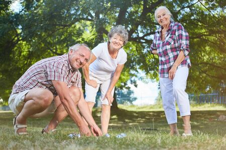 Seniors play boule or bocce together in the garden in summer in the retirement home