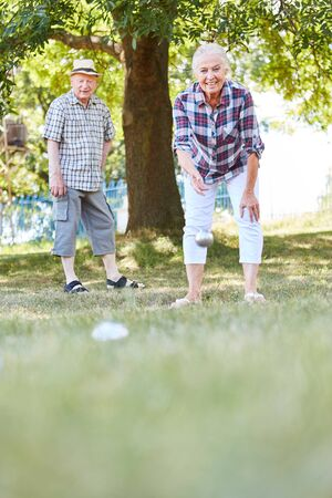 Seniors couple playing boule or bocce in the garden on vacation or in the retirement home Stock Photo