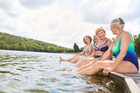 Group of seniors at the lake shore relaxes their feet in the water in summer on vacation