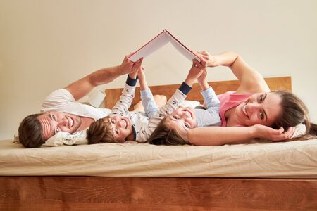 Family with two children read a book together on the bed in the bedroom