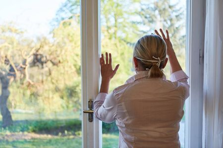 Elderly woman at the window at home during lockdown quarantine due to coronavirus pandemic looks outside