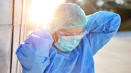 Employees in protective clothing during coronavirus pandemic put on face mask in front of clinic after break