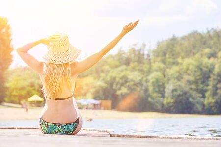 Young woman in bikini sunning at the dock of a bathing lake in summer