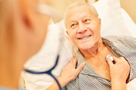 Senior man is listening to the stethoscope while visiting a doctor Banco de Imagens
