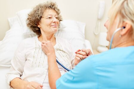 Nurse controls breathing with the stethoscope in a senior patient