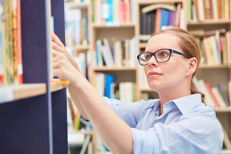 Woman as a librarian looks for book on shelf of a library of the community college or the university