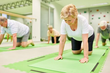 Senior citizens do back exercises at rehabilitation sports in physiotherapy
