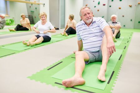Group of seniors on yoga mats at the rehabilitation sport in the physiotherapy class in the Pilates studio