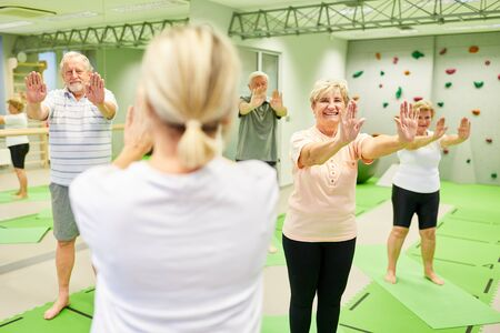 Vital seniors do back exercises with trainer or physiotherapist as rehabilitation