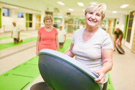 Smiling senior woman with the Bosu Ball in a physiotherapy course as a rehab sport