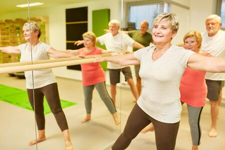 Group of sporty seniors doing rehabilitation at the ballet bar in physiotherapy