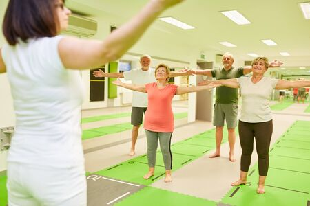 Instructors and seniors stretch their arms in back exercise as a physiotherapy exercise