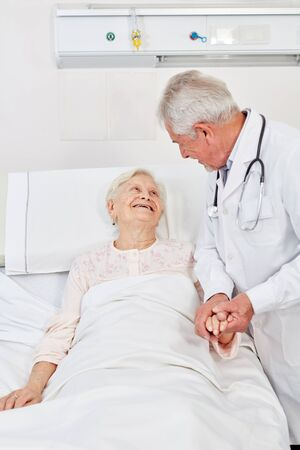 Sick and bedridden elderly woman is treated by a doctor and comforted