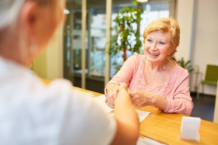 Older woman as a patient is greeted by a receptionist at the doctor with a handshake