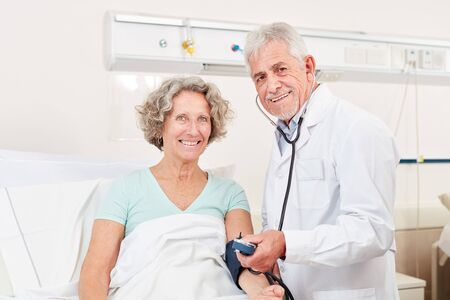 Doctor with sphygmomanometer at the bedside of a senior citizen in the hospital