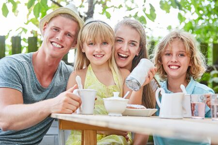 Happy family having coffee in garden with lots of sugar