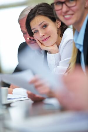 Business people sitting together at table in conference room at meeting