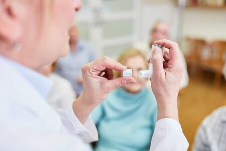 Doctor explains to senior citizens a dosing inhaler in a health course in a nursing home