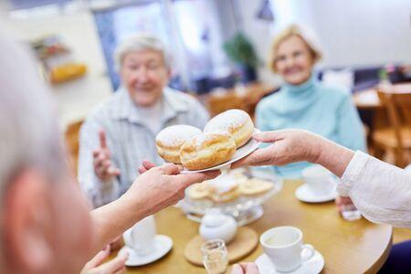 Seniors eat fresh Berlin pancakes in the common room in the retirement home Reklamní fotografie