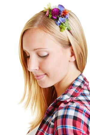 Young blonde woman with flower arrangement in her hair