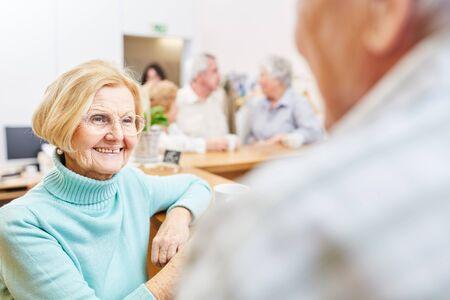 Smiling senior woman having small talk in retirement home or taking a break in the office Reklamní fotografie