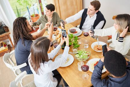 Rude friends all look at their smartphone at lunch at the table