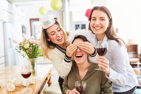 Laughing girlfriends are planning a surprise hen party for the bride