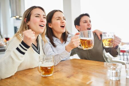 Group of women watch football and drink beer and cheer on their team