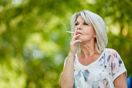 Old woman smoking a cigarette in nature Standard-Bild