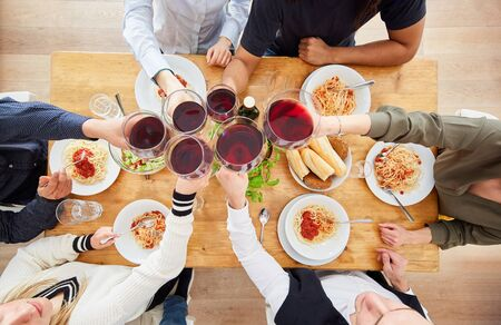 Group of friends toasting with glass of wine at dinner with spaghetti and tomato sauce Archivio Fotografico