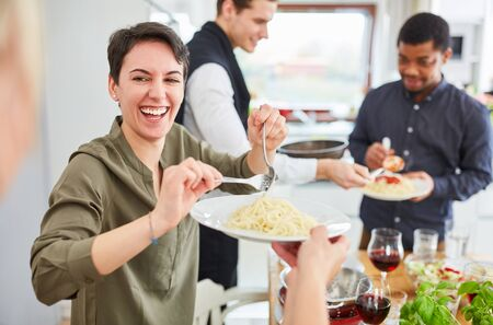 Young laughing woman serves pasta with tomato sauce in shared apartment for lunch Reklamní fotografie