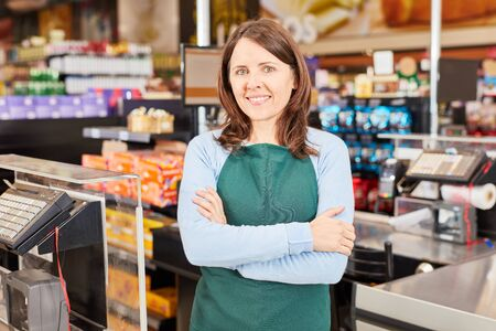 Young woman as a cashier or assistant in the supermarket with crossed arms