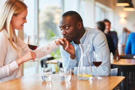 African man on date in the restaurant while flirting with his girlfriend Фото со стока