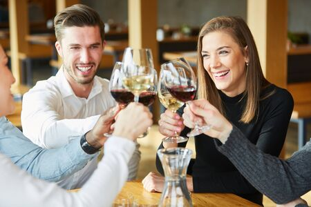 Young people toast with glass of wine in the restaurant and celebrate together