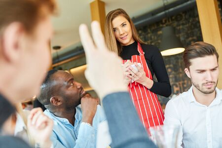 Young man as a guest raises his hand when ordering in a bar or bistro