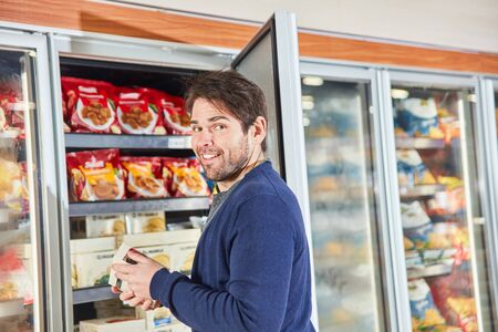 Man as a customer while shopping frozen food in the refrigerated shelf in the supermarket Reklamní fotografie