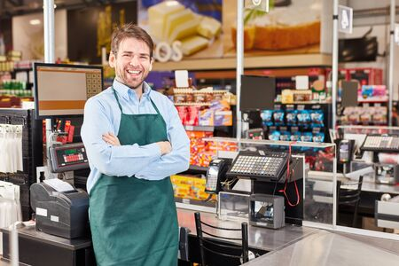 Cheerful man as a cashier with crossed arms in the supermarket at the cash register