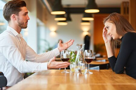Young couple having a rendezvous in the restaurant while discussing and arguing Foto de archivo