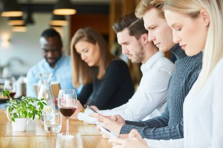 Young people with cell phone addiction in the restaurant are constantly staring at their smartphone