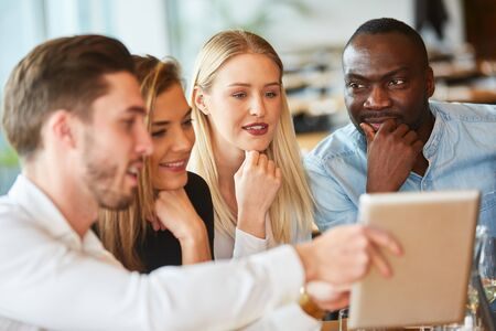 Young people in the restaurant look together on a tablet computer