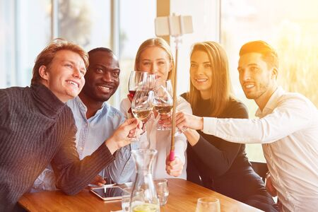 Friends take pictures with selfie stick in the restaurant over a glass of wine Фото со стока