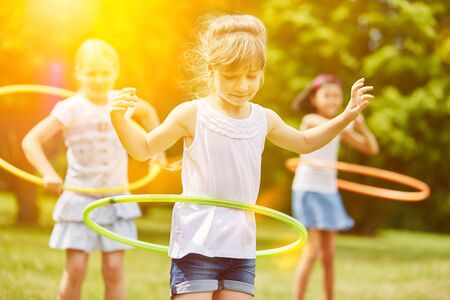 Three children play with tires in kindergarten in summer