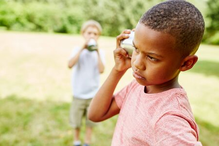 Two children play with a can phone in summer